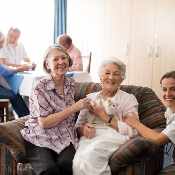 Portrait of female practitioner with kitten at nursing home