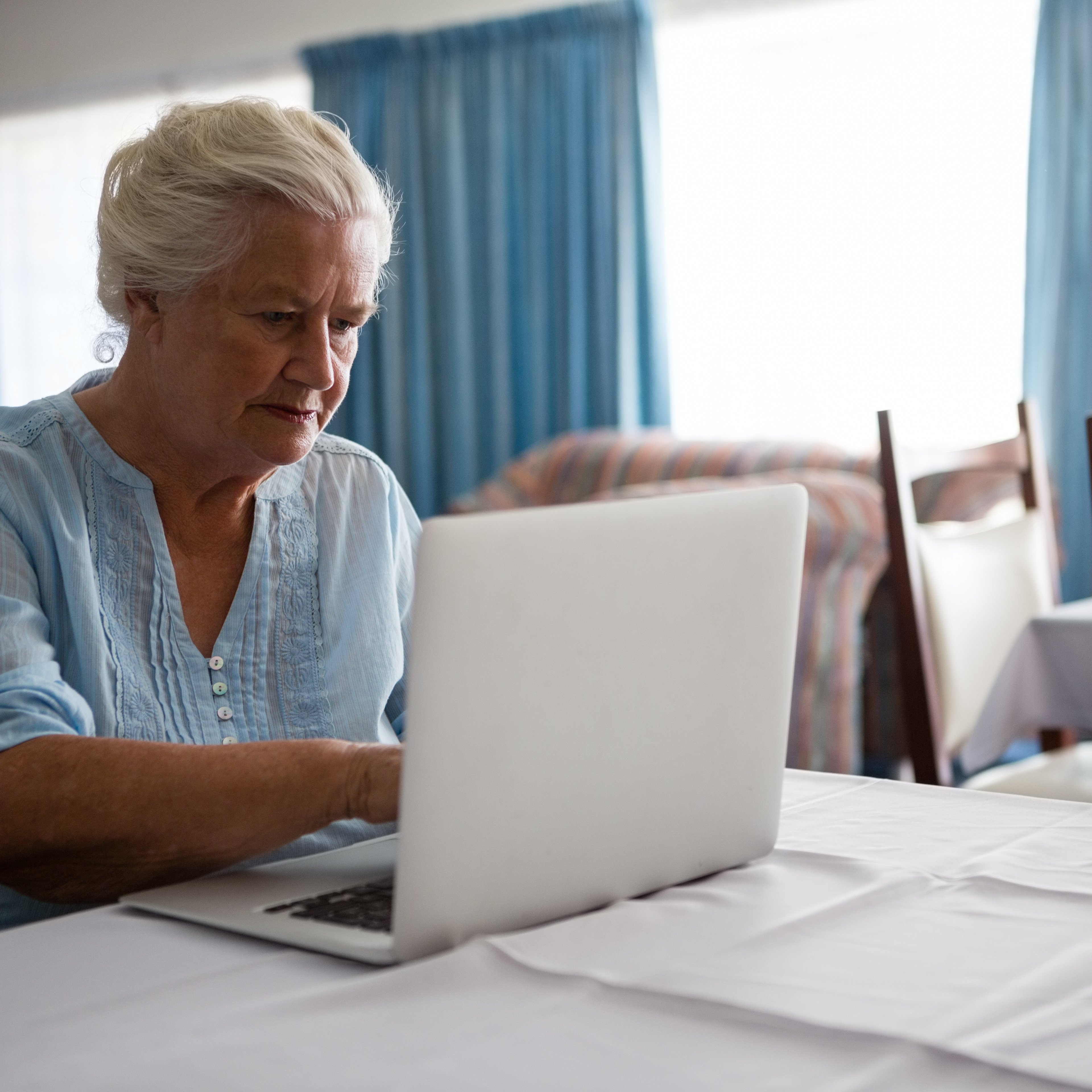 Senior woman using laptop while sitting at table in nursing home